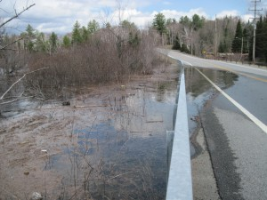 Water from Long Lake seeps over Route 30